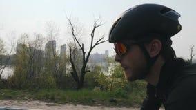 Νέος ποδηλάτης με τη γενειάδα που φορά τα γυαλιά ηλίου, το κράνος και τη μαύρη εξάρτηση που οδηγούν ένα ποδήλατο Κλείστε επάνω τη απόθεμα βίντεο