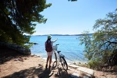 Νέος ποδηλάτης τουριστών γυναικών με το ποδήλατο πόλεων στην κωμόπολη κοντά στη θάλασσα στοκ εικόνα