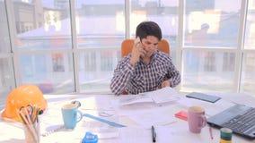 Νέος πολυάσχολος επιχειρηματίας που εργάζεται με τα σχέδια, σχεδιαγράμματα σε ένα ελαφρύ, σύγχρονο γραφείο φιλμ μικρού μήκους