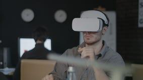 Νέος προγραμματιστής που χρησιμοποιεί vr τα γυαλιά Σχεδιαστής που εξετάζει το τρισδιάστατο παιχνίδι στο γραφείο νύχτας φιλμ μικρού μήκους