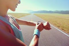 Νέος δρομέας γυναικών έτοιμος να τρέξει το σύνολο και την εξέταση το αθλητικό έξυπνο ρολόι Στοκ φωτογραφία με δικαίωμα ελεύθερης χρήσης