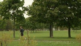 Νέος δρομέας στο πάρκο Ημέρα φθινοπώρου Ομαλός μετακινηθείτε τον πυροβολισμό απόθεμα βίντεο