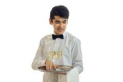Νέος σερβιτόρος ατόμων brunette με τη σαμπάνια στο χαμόγελο δίσκων Στοκ Φωτογραφίες