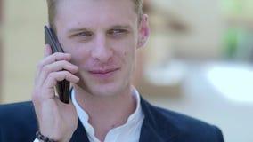 Νέος σκεπτικός επιχειρηματίας που μιλά στο τηλέφωνο υπαίθρια φιλμ μικρού μήκους