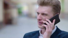 Νέος σκεπτικός επιχειρηματίας που μιλά στο τηλέφωνο υπαίθρια απόθεμα βίντεο