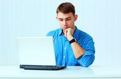 Νέος σκεπτικός επιχειρηματίας στην μπλε συνεδρίαση πουκάμισων στον πίνακα με το lap-top Στοκ φωτογραφίες με δικαίωμα ελεύθερης χρήσης