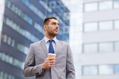 Νέος σοβαρός επιχειρηματίας με το φλυτζάνι εγγράφου υπαίθρια Στοκ Εικόνα