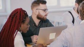 Νέος σοβαρός καυκάσιος προγραμματιστής λογισμικού που εργάζεται σε σύγχρονο με το lap-top, που ακούει στη multiethnic συνεδρίαση  απόθεμα βίντεο