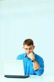 Νέος σοβαρός περιστασιακός επιχειρηματίας που εξετάζει το lap-top Στοκ Φωτογραφία