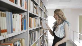 Νέος σπουδαστής που ψάχνει τα βιβλία στα ράφια και που παίρνει ενός απόθεμα βίντεο