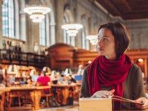 Νέος σπουδαστής στη βιβλιοθήκη στοκ εικόνες
