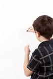 Νέος σπουδαστής αγοριών σε ένα γράψιμο σε ένα whiteboard Στοκ Φωτογραφία
