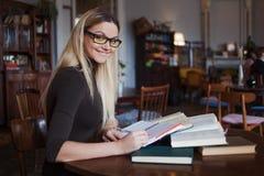 Νέος σπουδαστής γυναικών του πανεπιστημίου Προετοιμάζοντας το διαγωνισμό και μαθαίνοντας τη βιβλιοθήκη μαθημάτων δημόσια Στοκ Φωτογραφία
