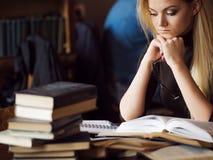 Νέος σπουδαστής γυναικών του πανεπιστημίου Προετοιμάζοντας το διαγωνισμό και μαθαίνοντας τη βιβλιοθήκη μαθημάτων δημόσια Στοκ Εικόνες