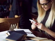 Νέος σπουδαστής γυναικών του πανεπιστημίου Προετοιμάζοντας το διαγωνισμό και μαθαίνοντας τη βιβλιοθήκη μαθημάτων δημόσια Στοκ Φωτογραφίες