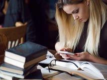 Νέος σπουδαστής γυναικών του πανεπιστημίου Προετοιμάζοντας το διαγωνισμό και μαθαίνοντας τη βιβλιοθήκη μαθημάτων δημόσια Στοκ Εικόνα