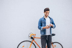 Νέος σπουδαστής που στέκεται κοντά στο ποδήλατο που εξετάζει το τηλέφωνο και που ακούει τη μουσική Στοκ φωτογραφία με δικαίωμα ελεύθερης χρήσης