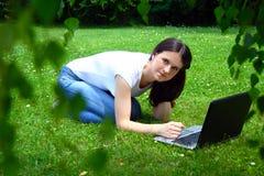 Νέος σπουδαστής YBeautiful που χρησιμοποιεί το lap-top στη χλόη Στοκ Εικόνα