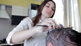 Νέος στιλίστας, κομμωτής που εφαρμόζει το χρώμα τρίχας σε μια γυναίκα Χρωματισμός τρίχας στο σκοτεινό χρώμα, διαδικασία απόθεμα βίντεο