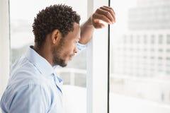 Νέος στοχαστικός επιχειρηματίας που κλίνει ενάντια σε ένα παράθυρο Στοκ Εικόνες
