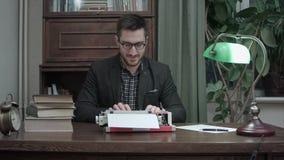 Νέος συγγραφέας στα γυαλιά που τρίβουν τα χέρια του και που αρχίζουν τη δακτυλογράφηση σε μια κόκκινη εκλεκτής ποιότητας γραφομηχ φιλμ μικρού μήκους