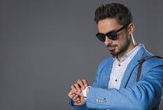 Νέος συγκεντρωμένος επιχειρηματίας που κοιτάζει στο ρολόι στοκ εικόνες