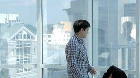 Νέος συντριμμένος επιχειρηματίας που ρίχνει τα έγγραφα, έγγραφα από το παράθυρο στο σπίτι απόθεμα βίντεο