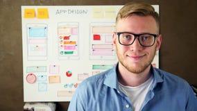 Νέος σχεδιαστής UX που χαμογελά στο δημιουργικό γραφείο αντιπροσωπειών απόθεμα βίντεο
