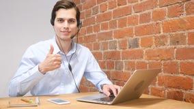 Νέος σύγχρονος επιχειρηματίας που διεγείρεται με την επιτυχία του που δίνει τους αντίχειρες επάνω, τηλεφωνικό κέντρο στοκ φωτογραφία