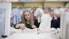 Νέος σύζυγος με τα έγκυα ενδύματα αγοράς συζύγων του για νεογέννητο στο μωρό και το κατάστημα μητρότητας φιλμ μικρού μήκους