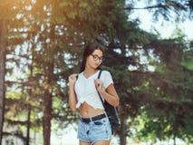 Νέος ταξιδιώτης γυναικών με το σακίδιο πλάτης που στέκεται μόνο στο δασικό κορίτσι Hipster στα ηλιόλουστα ξύλα στοκ εικόνες