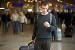 Νέος ταξιδιώτης που χρησιμοποιεί το κινητό τηλέφωνο στον αερολιμένα Στοκ φωτογραφία με δικαίωμα ελεύθερης χρήσης