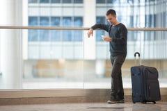 Νέος ταξιδιώτης που χρησιμοποιεί το smartphone στον αερολιμένα Στοκ φωτογραφίες με δικαίωμα ελεύθερης χρήσης