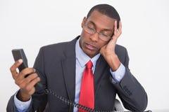 Νέος τεντωμένος νέος επιχειρηματίας Afro με το ακουστικό τηλεφώνου Στοκ Φωτογραφίες