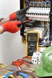 Νέος τεχνικός ηλεκτρολόγων στην εργασία για μια ηλεκτρική επιτροπή με Στοκ εικόνα με δικαίωμα ελεύθερης χρήσης