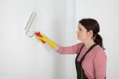 Νέος τοίχος χρωμάτων εργαζομένων σε ένα δωμάτιο στο λευκό Στοκ Φωτογραφία