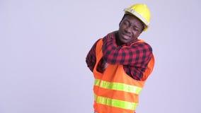 Νέος τονισμένος αφρικανικός εργάτης οικοδομών ατόμων που έχει τον πόνο στην πλάτη φιλμ μικρού μήκους
