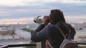Νέος τουρίστας γυναικών με το σακίδιο πλάτης που εξετάζει την πόλη μέσω των λειτουργουσών με κέρματα διοπτρών κατά τη διάρκεια το φιλμ μικρού μήκους