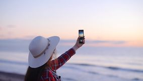 Νέος τουρίστας γυναικών που παίρνει τις εικόνες του ηλιοβασιλέματος ή της αυγής θαλασσίως φιλμ μικρού μήκους