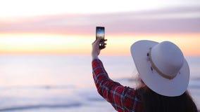 Νέος τουρίστας γυναικών που παίρνει τις εικόνες του ηλιοβασιλέματος ή της αυγής θαλασσίως απόθεμα βίντεο