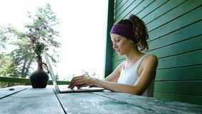 Νέος τουρίστας επιχειρησιακών γυναικών freelancer που δακτυλογραφεί σε ένα lap-top το καλοκαίρι υπαίθρια στο κέντρο αναψυχής απόθεμα βίντεο