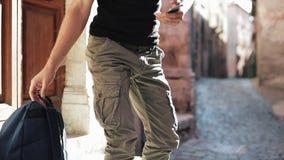 Νέος τουρίστας με τη συνεδρίαση σακιδίων πλάτης στα σκαλοπάτια εισόδων και τη χρησιμοποίηση του κινητού τηλεφώνου Ένας νεαρός άνδ απόθεμα βίντεο