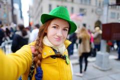 Νέος τουρίστας που παίρνει ένα selfie κατά τη διάρκεια της ετήσιας παρέλασης ημέρας του ST Πάτρικ στη Νέα Υόρκη Στοκ Φωτογραφίες
