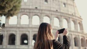 Νέος τουρίστας brunette που εξερευνά το Colosseum στη Ρώμη, Ιταλία Η γυναίκα παίρνει τη φωτογραφία της θέας, χρησιμοποιεί το smar απόθεμα βίντεο