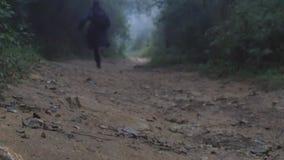 Νέος τύπος αδιάβροχων στο ξύλινο ίχνος κατά τη διάρκεια του ταξιδιού Πεζοποριες άτομο με το σακίδιο πλάτης που τρέχει στο τροπικό φιλμ μικρού μήκους