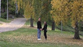 Νέος τύπος με έναν περίπατο κοριτσιών στο πάρκο, που κρατά τα χέρια απόθεμα βίντεο
