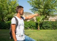 Νέος τύπος με το σακίδιο πλάτης, τουρίστας που δείχνει στις καταστροφές του CI Στοκ Εικόνα