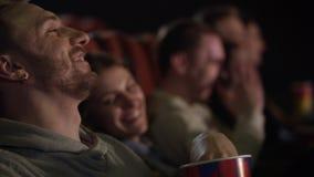 Νέος τύπος με το σκουλαρίκι στο αυτί του που τρώει popcorn που γελά κατά την προσοχή του κινηματογράφου απόθεμα βίντεο