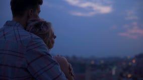 Νέος τύπος που αγκαλιάζει ήπια τη φίλη του από τους ώμους που θερμαίνουν την στο ηλιοβασίλεμα απόθεμα βίντεο