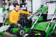 Νέος τύπος που αποφασίζει σχετικά με τον καλύτερο χορτοκόπτη στο κατάστημα εξοπλισμού κήπων Στοκ φωτογραφία με δικαίωμα ελεύθερης χρήσης